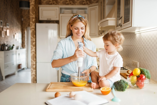 Mother and daughter whisk ingredients with blender