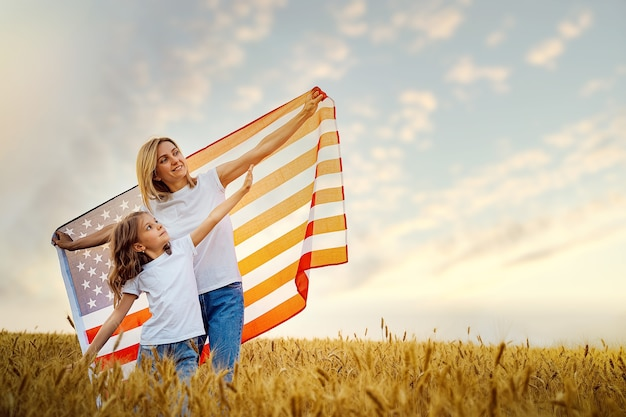 Mother and daughter with american flag in a beautiful wheat field
