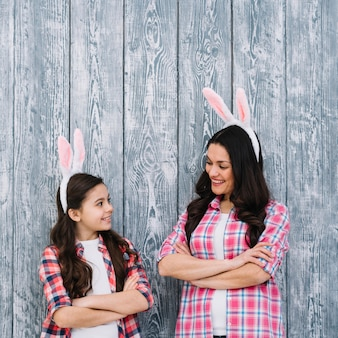Mother and daughter with arms crossed looking at each other against wooden gray backdrop