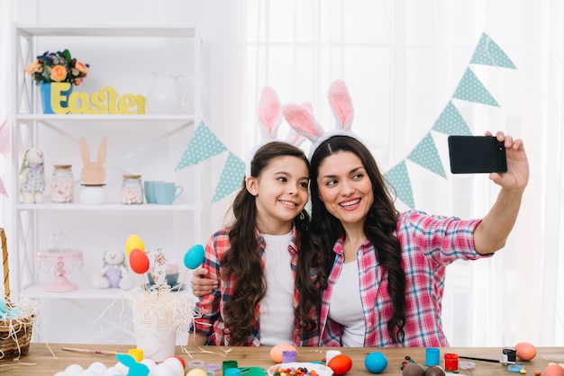 Mother and daughter with bunny ears taking selfie on mobile phone at home