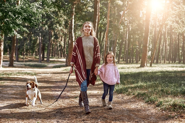 Mother and daughter with dog hiking in pine forest. woman is wearing a stylish knitted coat, girl is in pink bright sweater