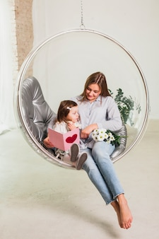 Mother and daughter with greeting card in hanging chair