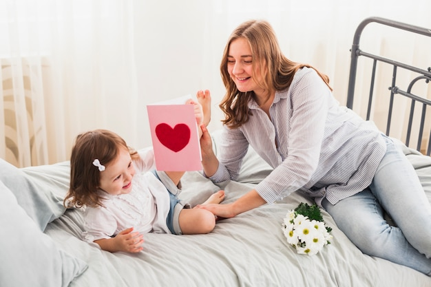 Mother and daughter with greeting card having fun