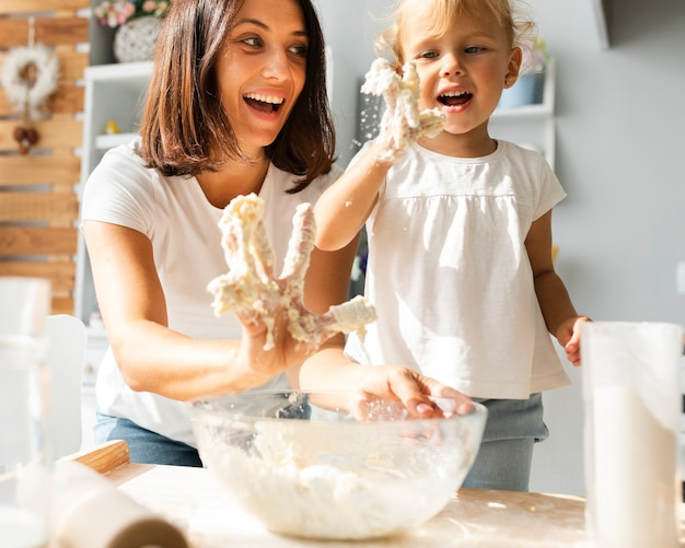 Mother and daughter with hands full of dough