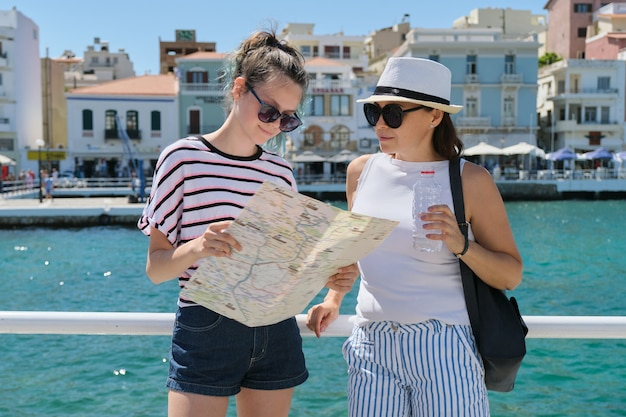 Mother and daughter with map on sunny day near sea promenade