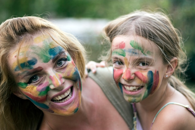 Mother and daughter with painted faces having fun in the garden