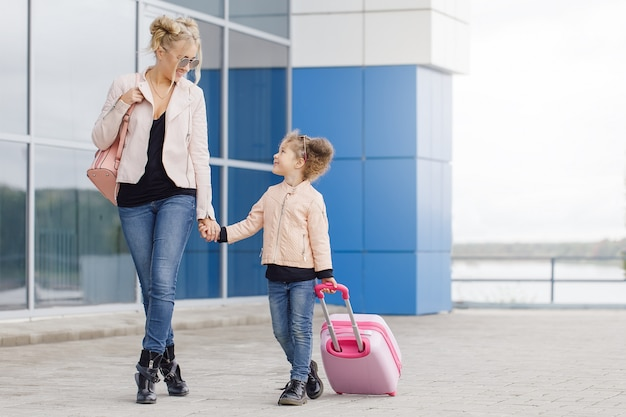 Mother and daughter with pink luggage in pink jacket against the airport.