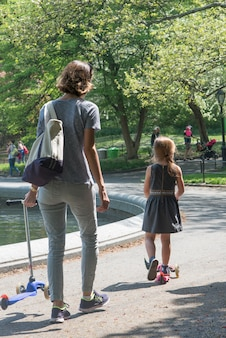 Mother and daughter with push scooter in central park, manhattan, new york city, new york state, usa