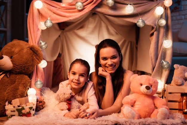 Mother and daughter with teddy bears in pillow house.