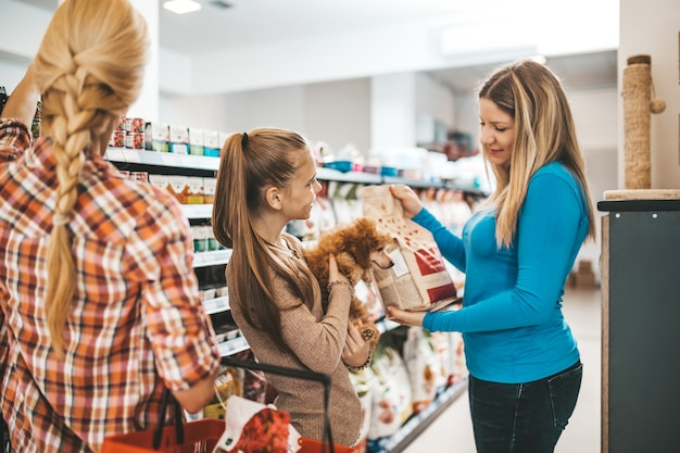 Mother and daughter with their poodle puppy in pet shop.