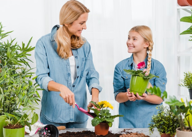 Mother and daughter working together in greenhouse