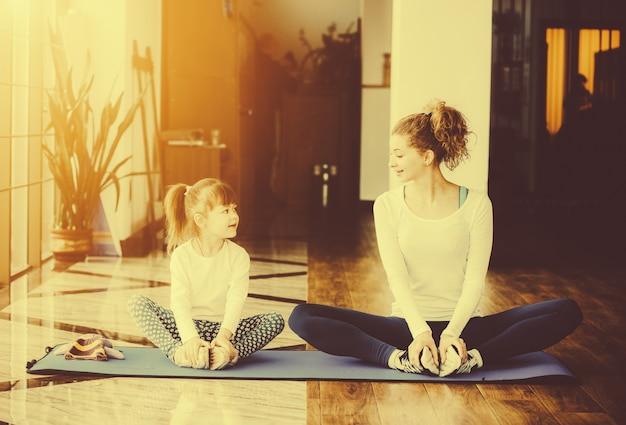 Madre e figlia in posa yoga seduto su una stuoia