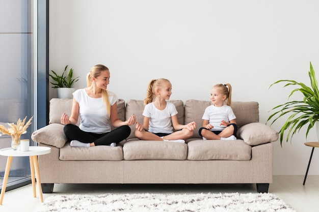Mother and daughters exercising at home on couch