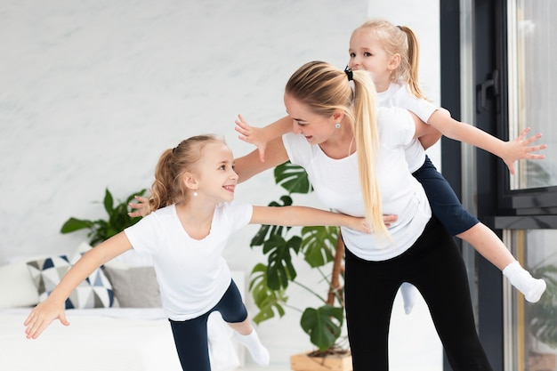 Mother and daughters at home exercising