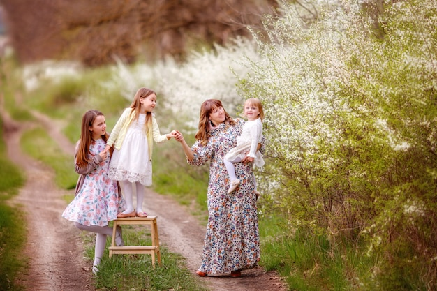 Mother and daughters near a flowering bush, spring, spring family photo shoot