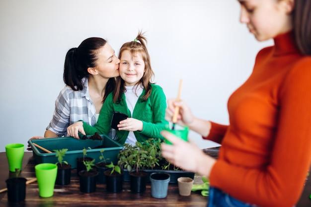 屋内で苗を植える母娘
