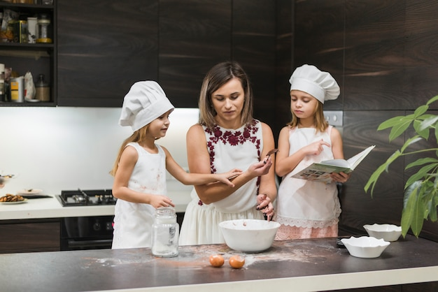 Mother and daughters preparing food in kitchen