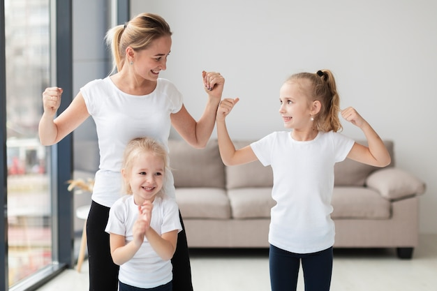 Mother and daughters showing off they biceps at home