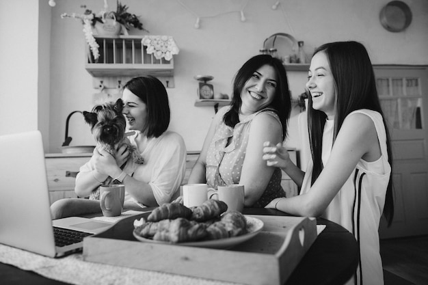 Mother and daughters talking and eating croissants in the kitchen .b&w