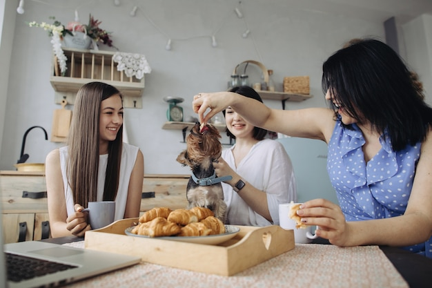 Mother and daughters talking and eating croissants in the kitchen