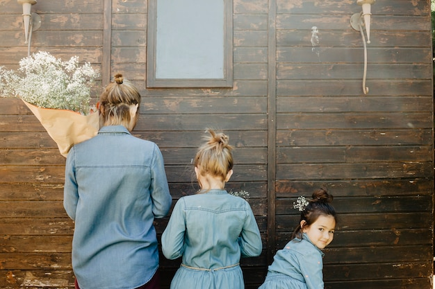 Mother and daughters with flowers near shed