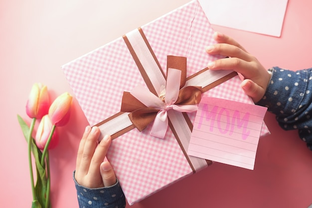 Mother day concept of child hand holding pink color gift box