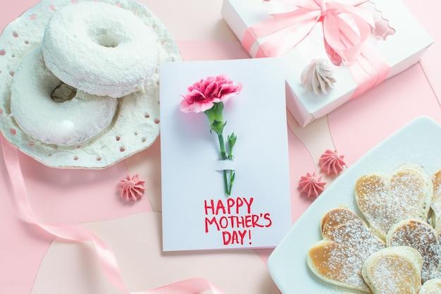 분홍색 테이블에 어머니의 날 인사말 카드 카드입니다. 텍스트 해피 어머니의 날. 아침 식사, 팬케이크, 카네이션, 선물, 엄마를 위해 아이가 만든 카드.