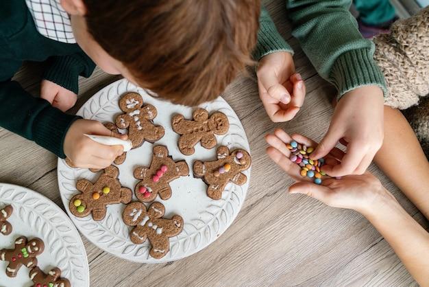 自宅で子供たちとジンジャーブレッドクッキーを飾る母