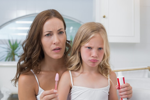 Mother and displeased daughter with toothbrush and toothpaste