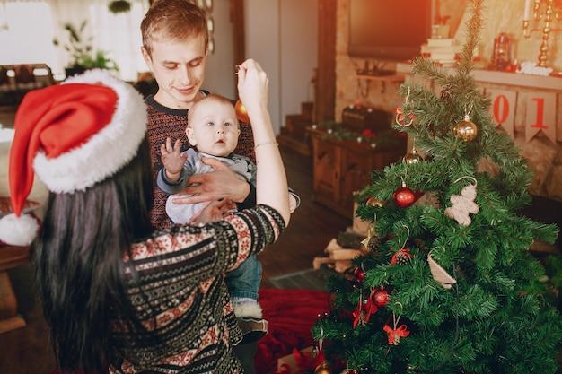 父は彼の腕の中でそれを保持しながら、母はクリスマスの飾りと赤ちゃんを邪魔します