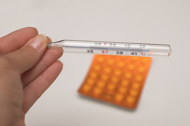 Мать-врач рука ртутный термометр с высокой температурой на фоне пачки таблеток. болезнь, лихорадка, грипп, вирус. лечение, понижение температуры. фото крупным планом