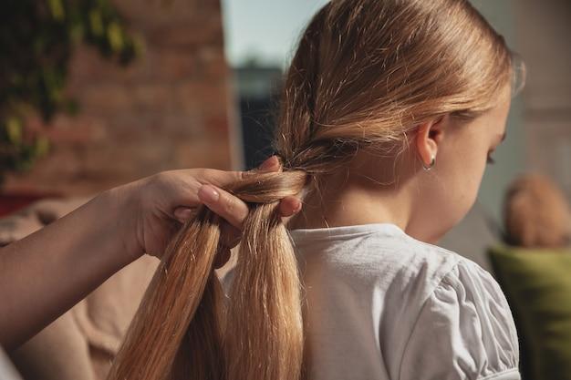 娘の髪に三つ編みをしている母親