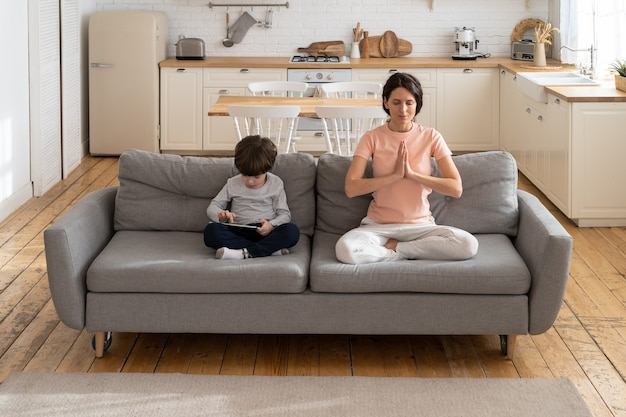 Mother doing yoga exercise, sitting on couch at home, child using gadget, playing a game on tablet.