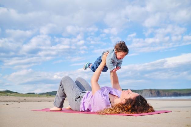 어머니는 해변에서 그녀의 아기와 함께 요가 하 고