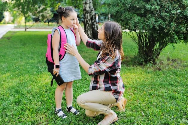 Мать одевает и отвозит дочь в школу обратно в школу в день знаний