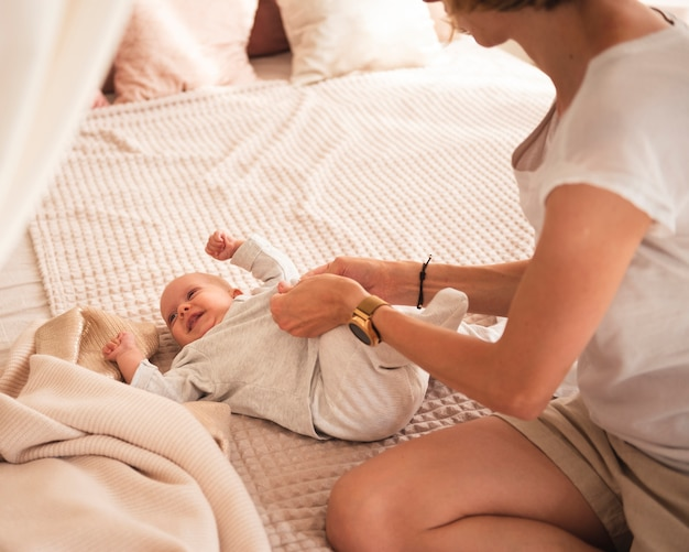 Mother dressing happy baby in bed
