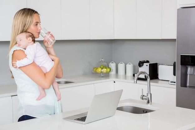 母は台所で赤ちゃんを運んでいる間水を飲む