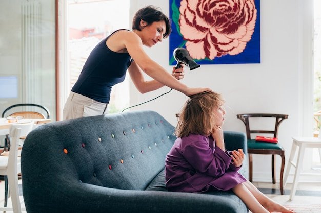 Mother drying the hair of her female child sitting on couch indoor at home