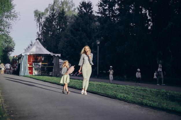 Madre mangiare un gelato e la figlia nuvola rosa mentre si cammina