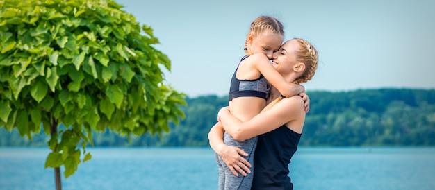 Мать обнимает свою дочь возле пруда в спортивной одежде на открытом воздухе