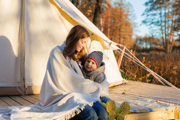 Mother embracing her kid with a blanket while sitting near camping tent