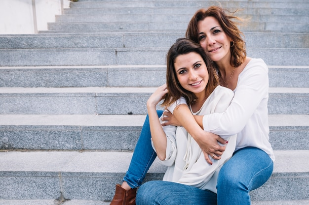 Mother embracing woman and looking at camera