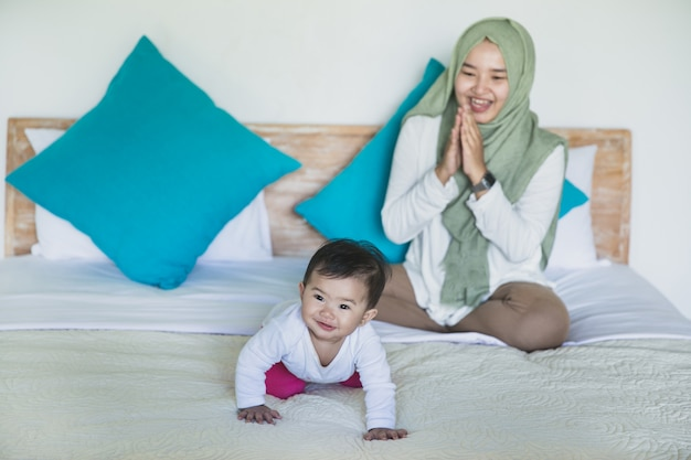 Mother encourage her baby to crawl
