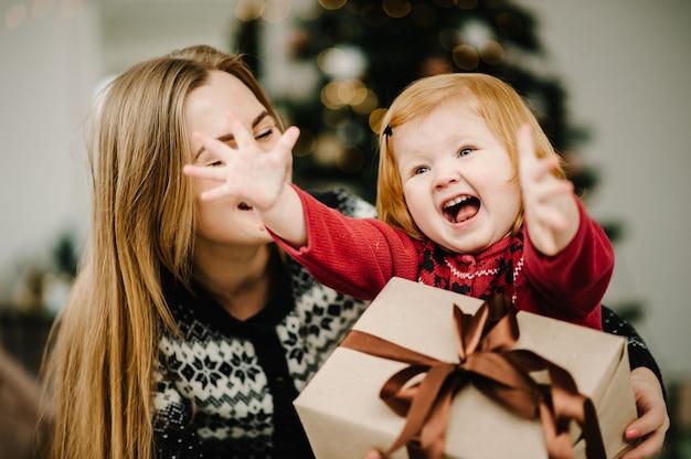 母は娘と贈り物を交換します親と子は屋内でクリスマスツリーの近くで楽しんでいます