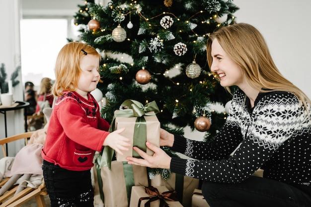 Мать обменивается подарками с дочерью родитель и ребенок веселятся возле елки