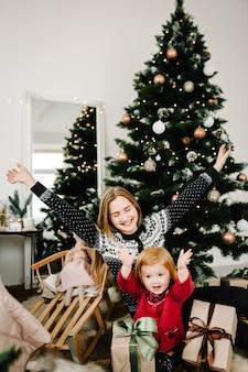 Мать обменивается подарками с дочерью родитель и маленький ребенок веселятся возле елки в помещении