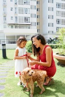 화창한 날 야외에 서 있을 때 가죽 끈에 개와 함께 걷는 방법을 어린 딸에게 설명하는 어머니