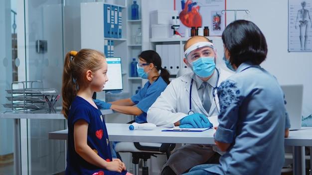 診療所でのコロナウイルス感染時の少女の症状を医師に説明する母親。医療サービスの相談、病院のキャビネットでの治療を提供するマスクを備えた医学の小児科医の専門家