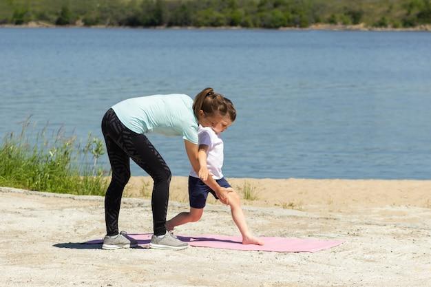 Мать объясняет и показывает маленькому сыну гимнастические упражнения на розовой циновке у моря.