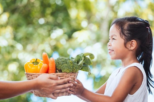 庭の小さな子供の女の子の手に野菜のバスケットを与える母農夫の手